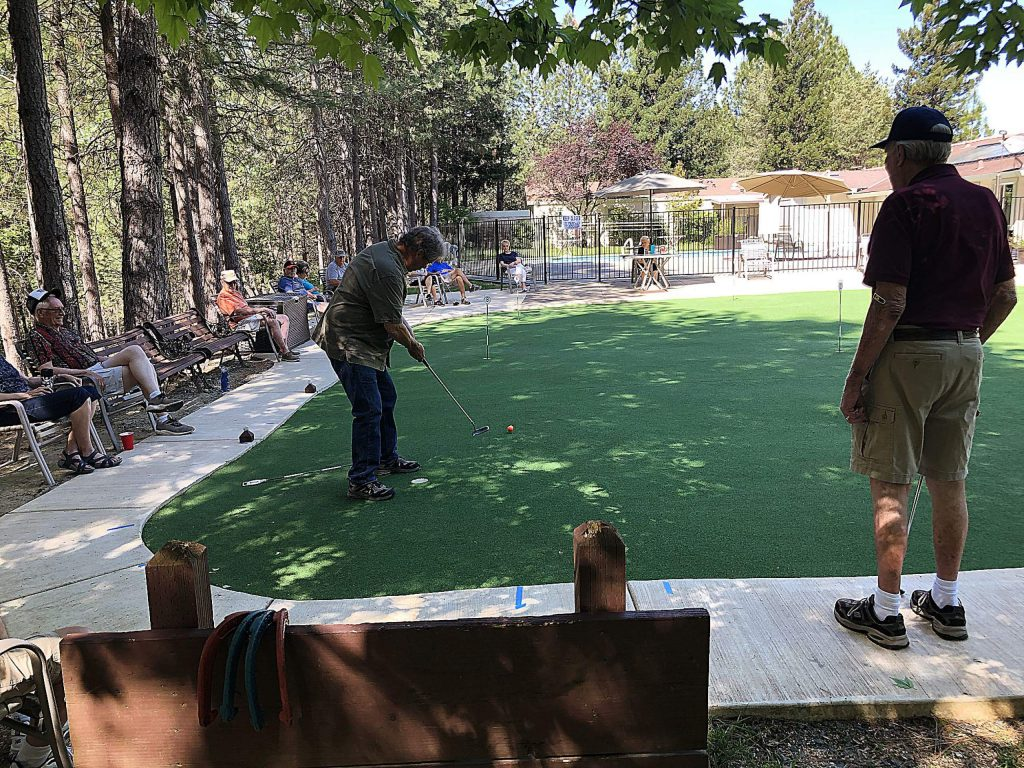 Tom Vanderleun, left, putts as Ed Smith looks on during a head-to-head match at the Ponderosa Pines putting green last Friday.