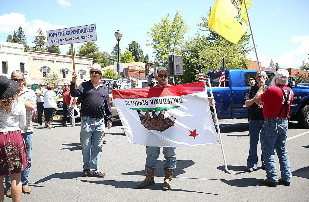 COVID-19 shutdown protesters hold flags and signs during Friday's ReOpen Nevada County rally in downtown Grass Valley.