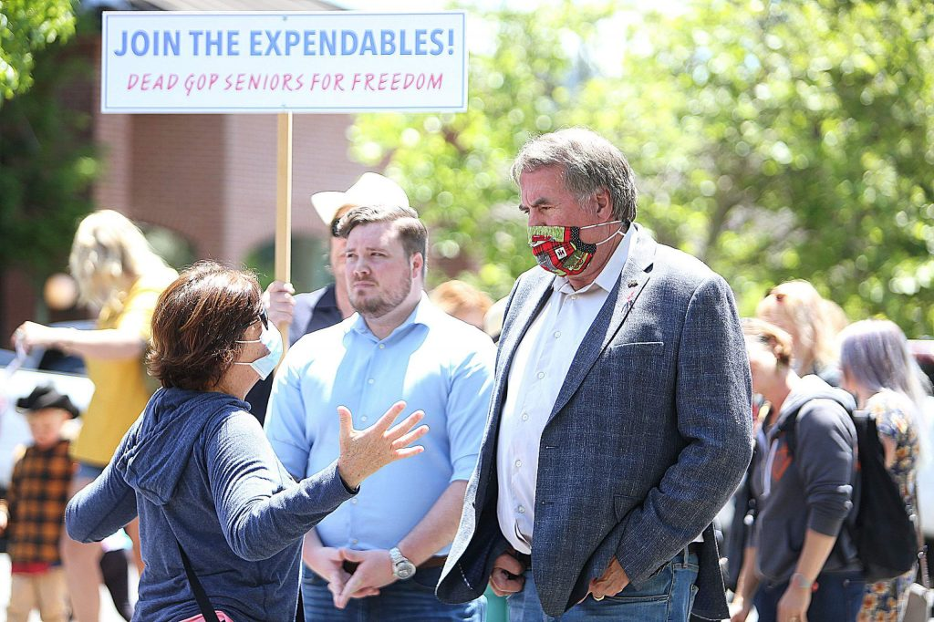 Congressman Doug LaMalfa dons a mask during portions of Friday's ReOpen Nevada County rally in Grass Valley.