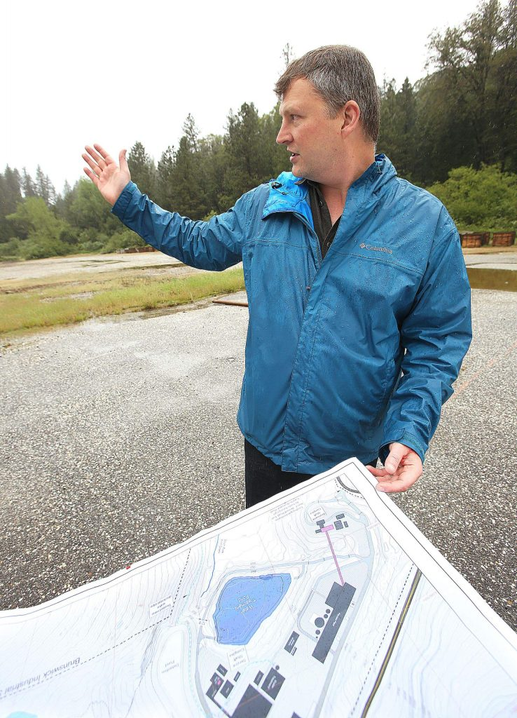 Mossman refers to a map of the site while explaining where elements of Rise Gold's production site would be constructed during a tour of the former Brunswick Mine site earlier this week.