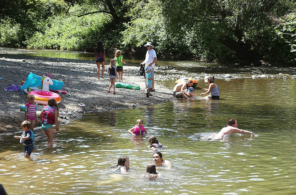 Children and adults take time to cool off in the calm waters of Penn Valley's Squirrel Creek Tuesday at Western Gateway Park where temperatures hit the mid 90s. Temps will remain in the mid to upper 90s today and tomorrow.