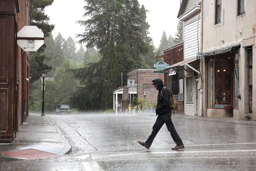 A pedestrian walks across a rain laden Pine Street during a late afternoon thunderstorm in Nevada City Saturday.