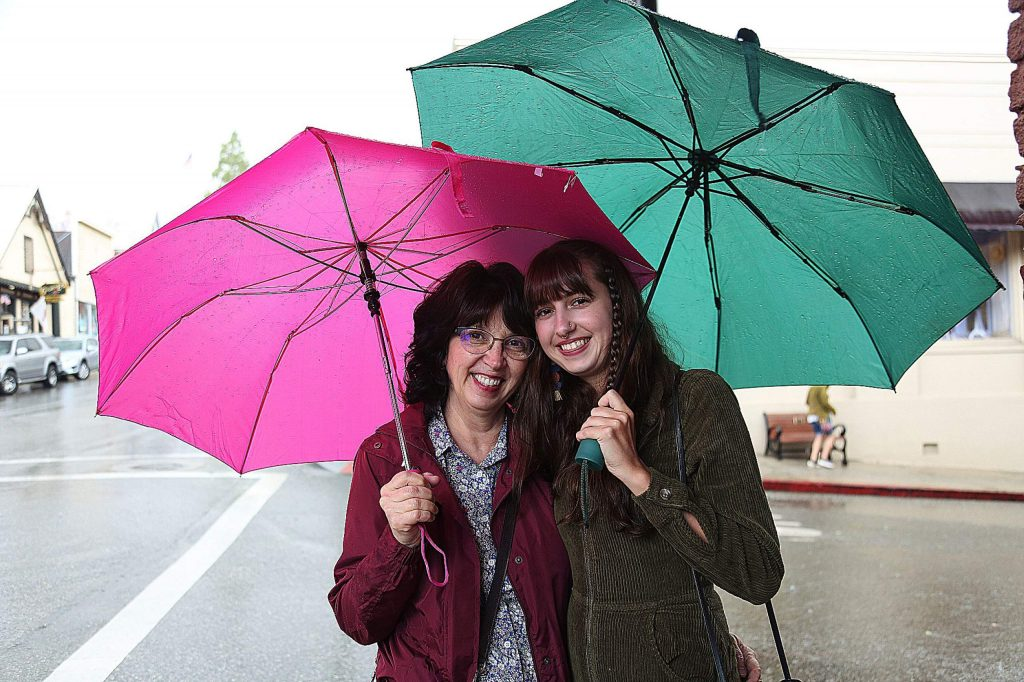 Grass Valley's Terri Sam and Sierra Slaton smile from under their umbrellas while window shopping Saturday in Nevada City.