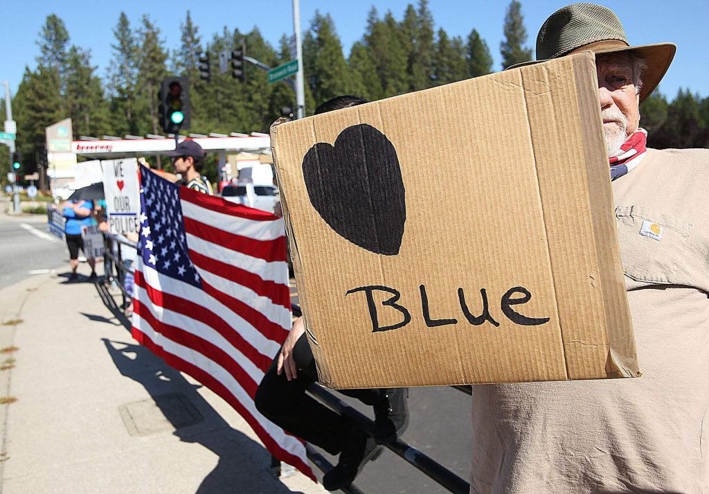 A man holds a cardboard sign showing his support for law enforcement Wednesday at the intersection of Sutton and Brunswick Road in Grass Valley.