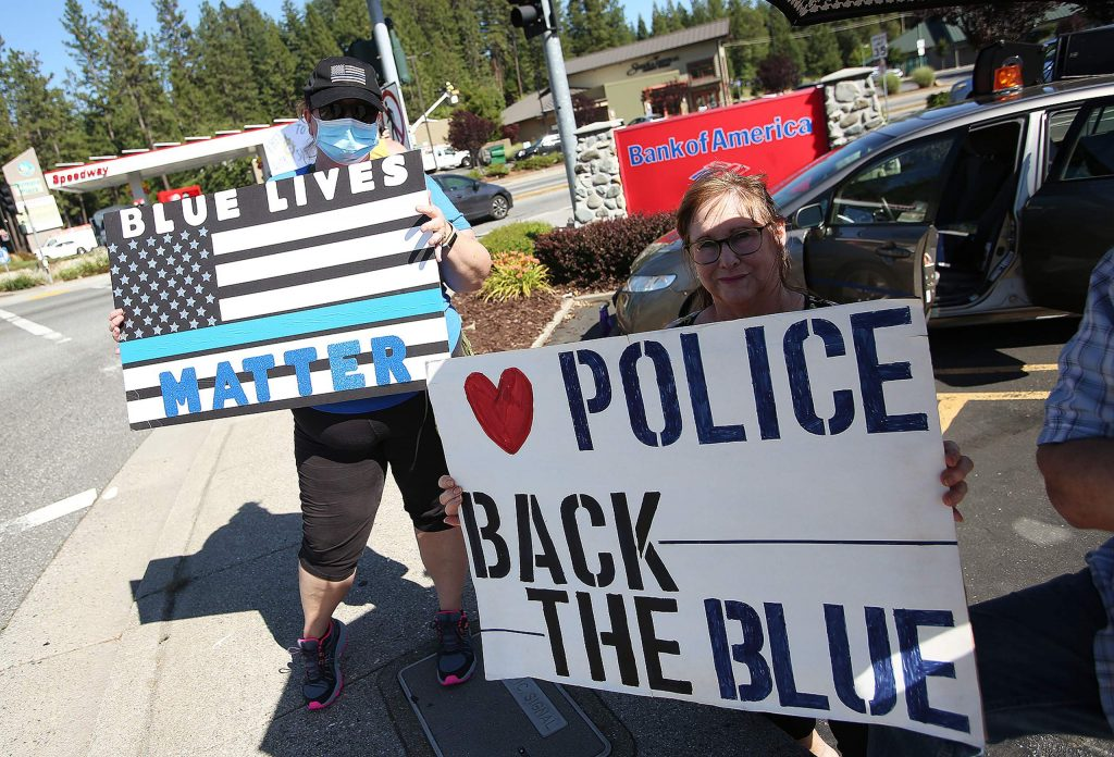 Blue Lives Matter and Back the Blue signs are held at the intersection of Brunswick and Sutton Way during Wednesday's rally in support of law enforcement.