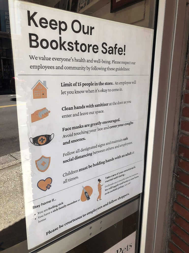 COVID-19 customer safety protocols are listed in the window of the Book Seller in Grass Valley.