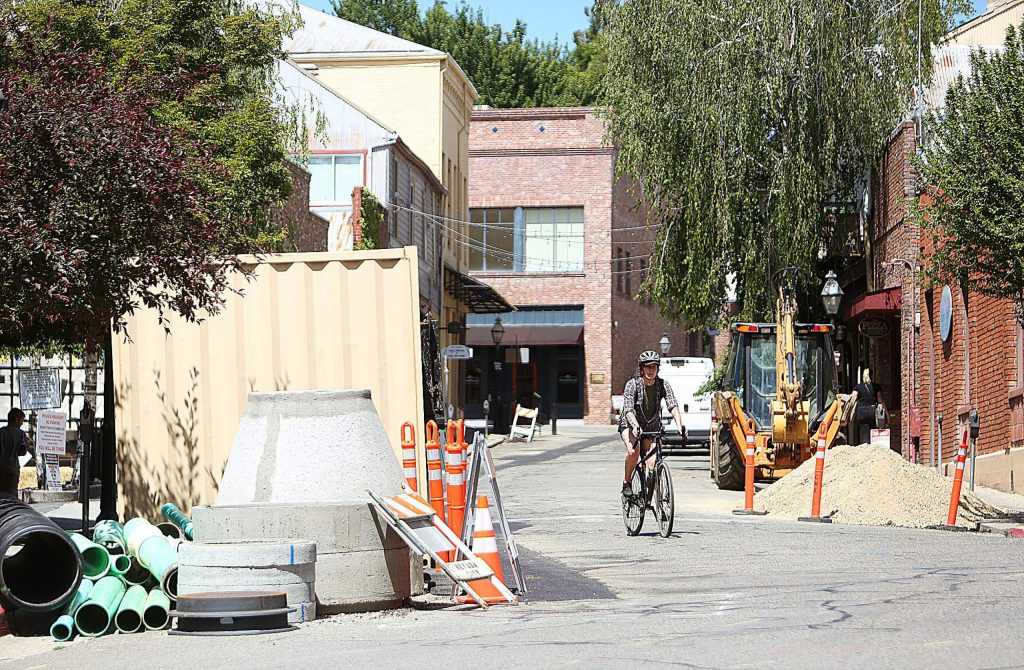 A cyclist navigates the construction materials left along Commercial Street in downtown Nevada City Tuesday.