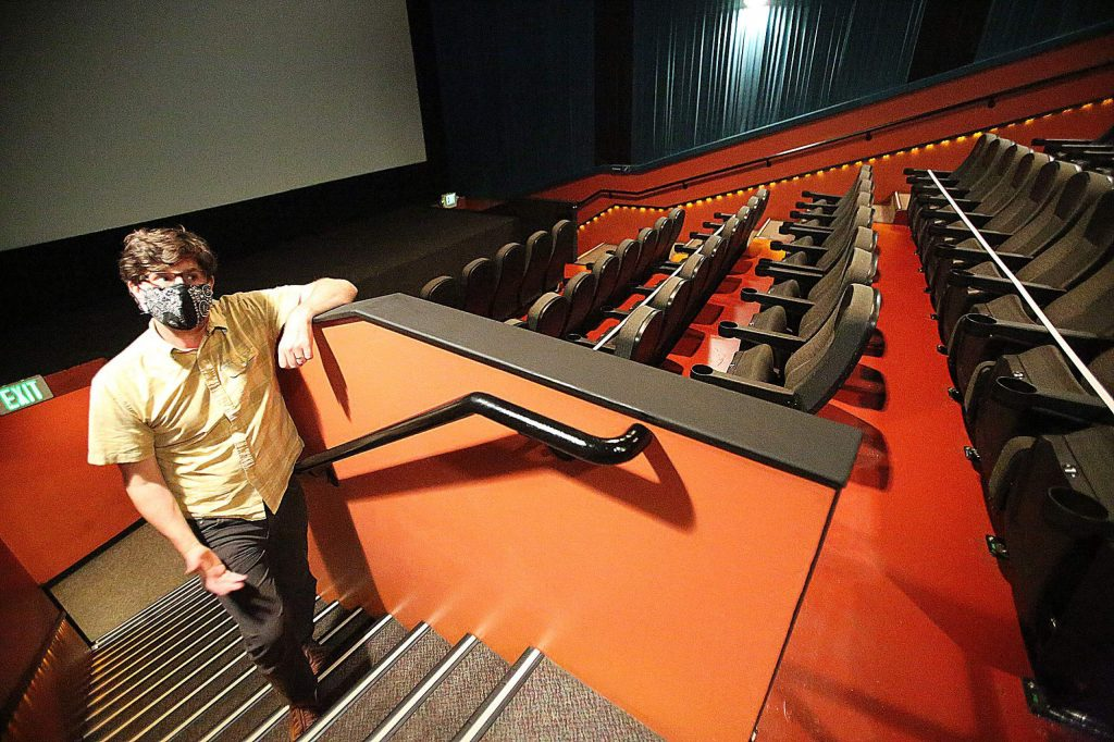 Del Oro Theater owner Michael LaMarca stands in one of the auditoriums where rows of seating have been marked off to help aid in social distancing.