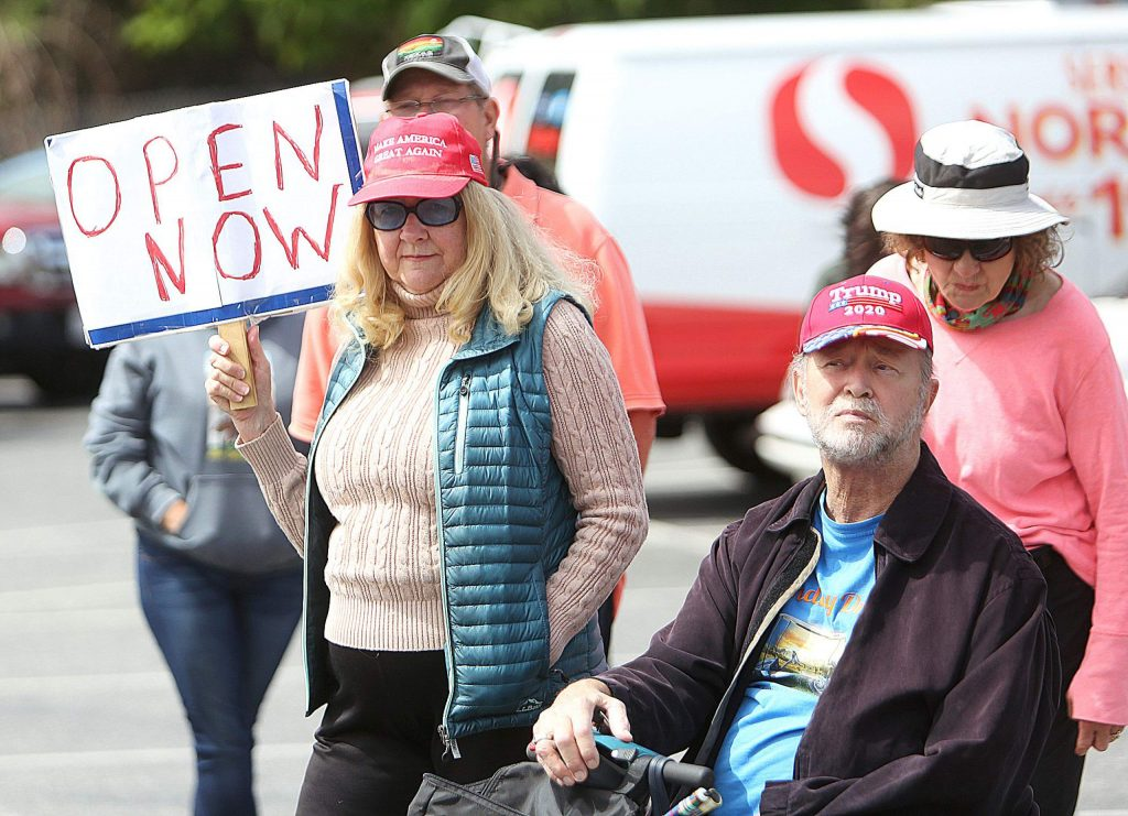 Protesters hold signs and listen to a selection of presenters during Saturday morning's rally in favor of hosting a fair on private property.