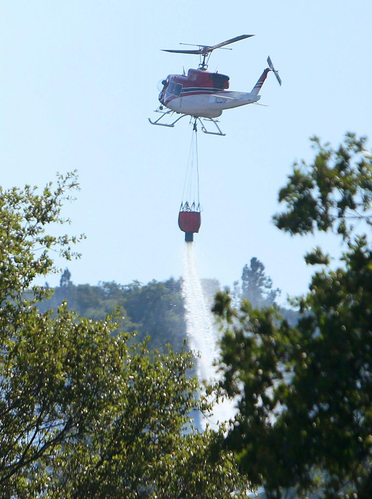 White Cloud helicopter 514 from the Tahoe National Forest makes one of many water drops on the Wildwood Fire Monday along Pleasant Valley Road near Lake Wildwood.