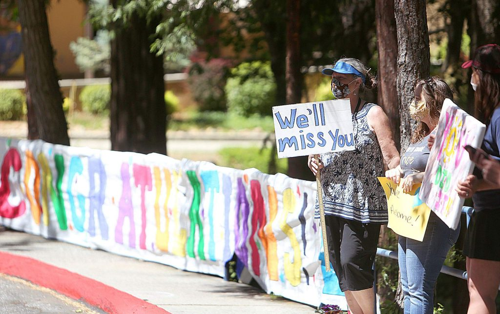 Teachers hold up signs for their students as they pass through Deer Creek Elementary School's parking lot Friday afternoon.
