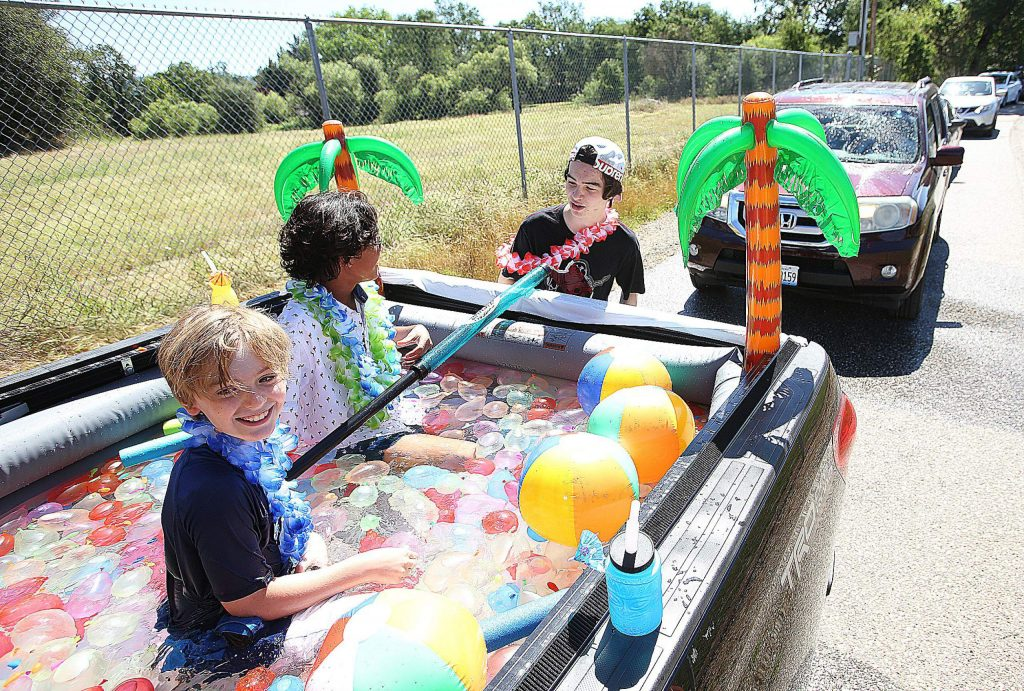 Members of the Zimmerman family kept cool in the back of a pickup truck turned into a pool filled with water balloons during Thursday's Ready Springs Elementary School drive-thru graduation ceremony.