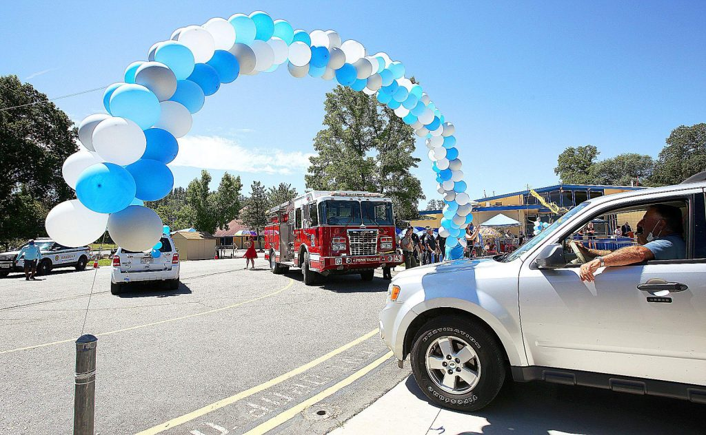 Vehicles pass under a balloon arch during Ready Springs Elementary School's eighth grade drive-thru graduation ceremony in Penn Valley.