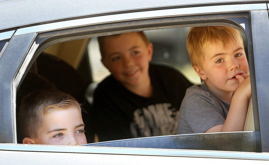 A group of siblings peek out the windows of their vehicle as they pass through Deer Creek Elementary School's clap out for third and fourth graders.