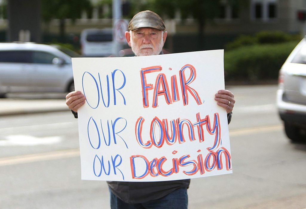A protester holds a sign for passersby on Neal and South Auburn streets during a protest about the 2020 Nevada County Fair cancellation, and to propose hosting a fair on private property. Fair board members made the decision to cancel the fair ealier last month.