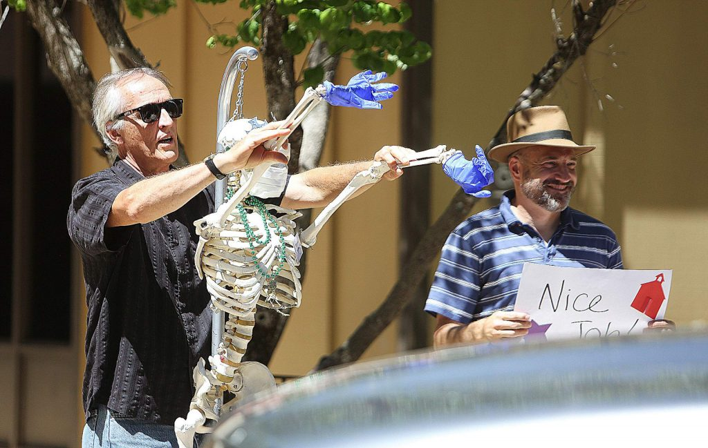 STEAM teacher Russ Osman-Bravard waves at passing students with the help of a skeleton during Friday's clap out at Deer Creek Elementary School.