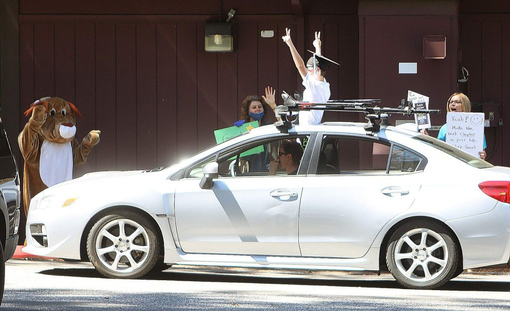 A Deer Creek fourth grader puts up the peace signs as he passes through Friday afternoon's drive-thru promotion ceremony at the Nevada City school.