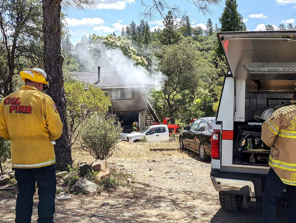 Cal Fire and Grass Valley fire chiefs direct Tuesday's firefighting operations at the garage fire along the 15000 block of Wolf Mountain Road.