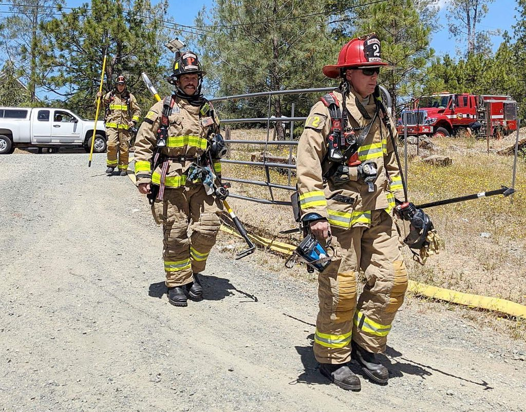 Firefighters approach the scene of Tuesday's structure fire to help with knockdown and any extension to adjacent wildlands. The fire never spread to the vegetation.