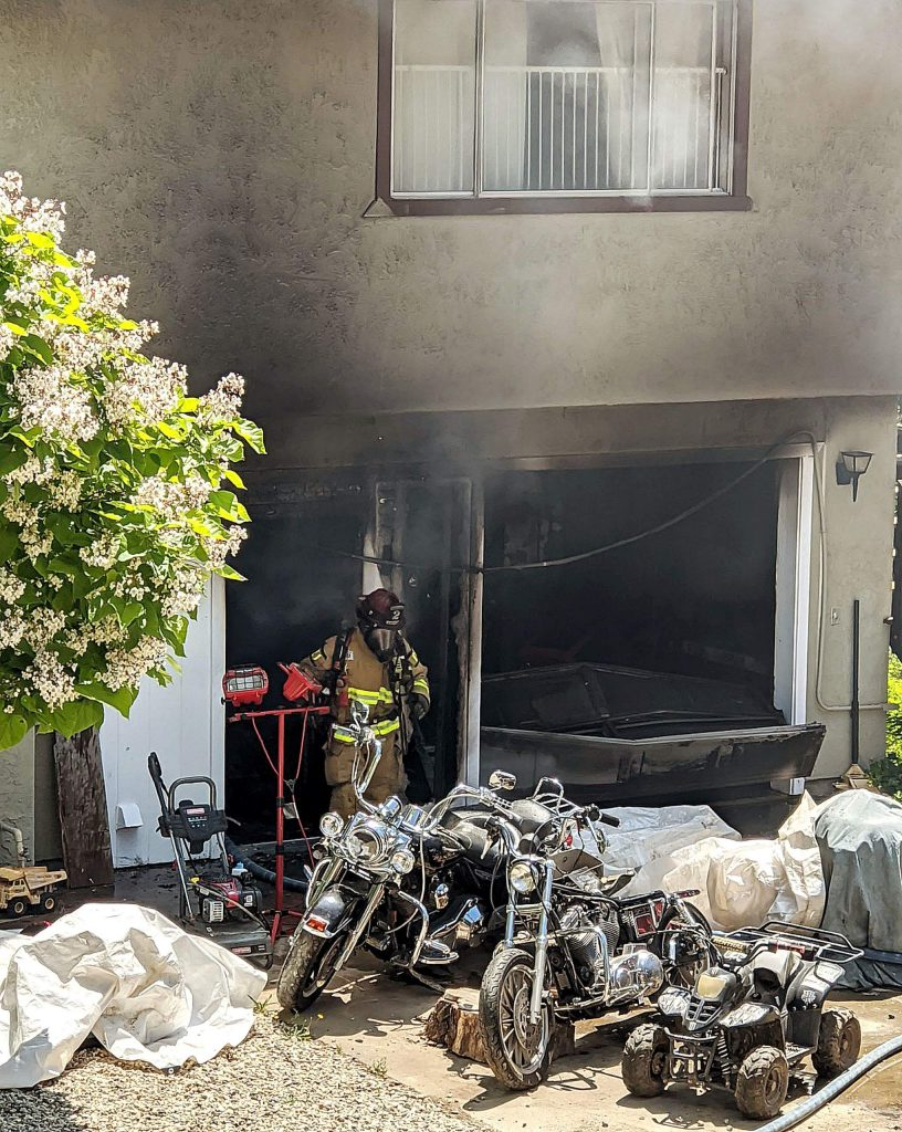 A firefighter emerges from a smoky garage off Wolf Mountain Road that caught fire Tuesday. Firefighters were able to contain the fire to the garage with minimal damage caused to the residential space above.