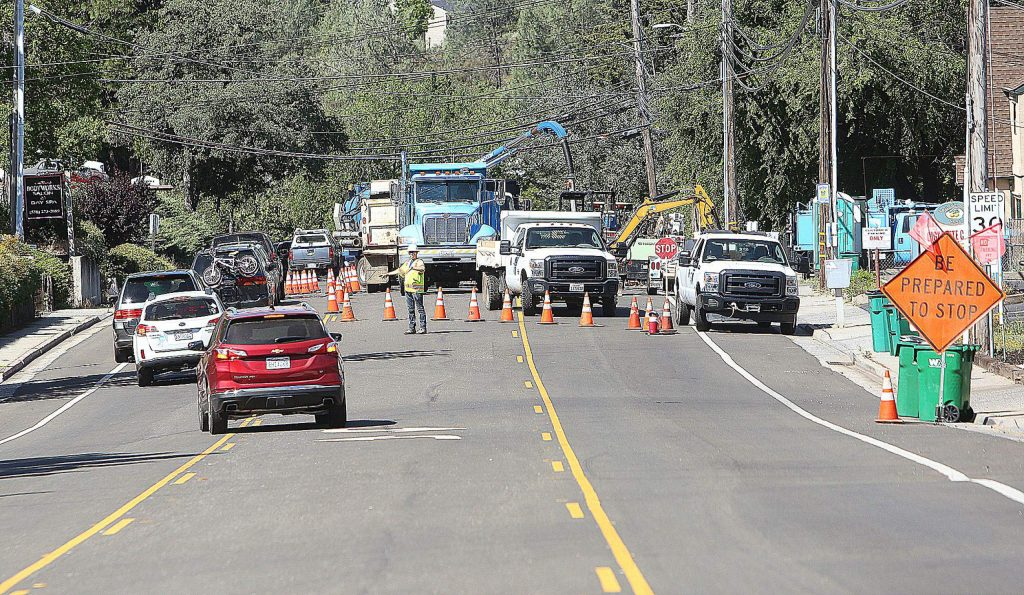 Flaggers direct one-lane traffic along East Main Street at Presley Way in Grass Valley where Nevada Irrigation District and PG&E workers are repairing a gas and water main leak.