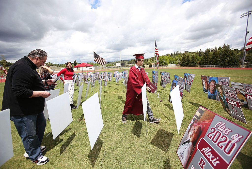 Graduates and family members search for their portrait in a crowd of poster board pupils following their walk though ceremony last month at Bear River High School. Students were given a few minutes to take photos and enjoy the moment before the next graduation appointment is scheduled to walk through.