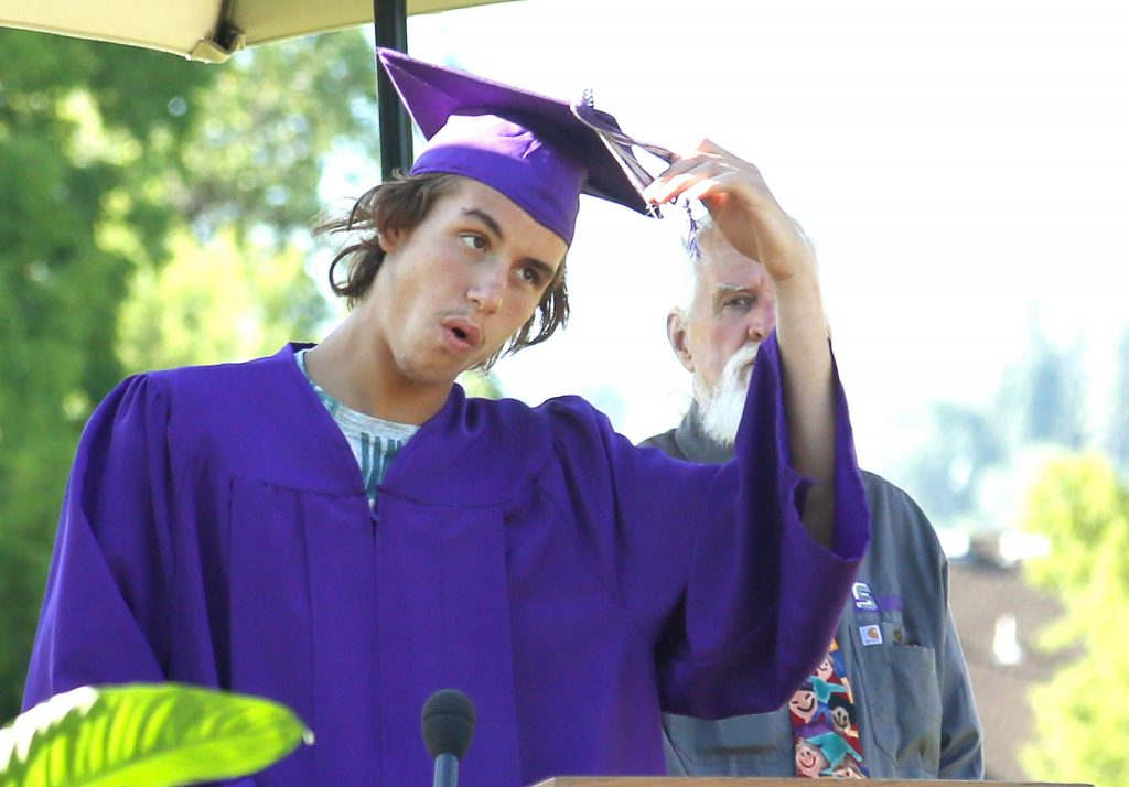 A Silver Springs High School graduate moves his tassel over to signify his graduation during last week's drive-thru ceremony in Grass Valley.