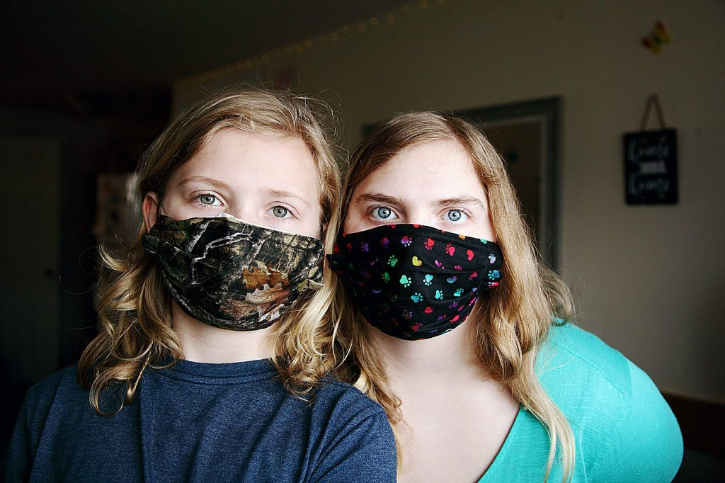 The McCutcheon children put on their masks to go outside to play.