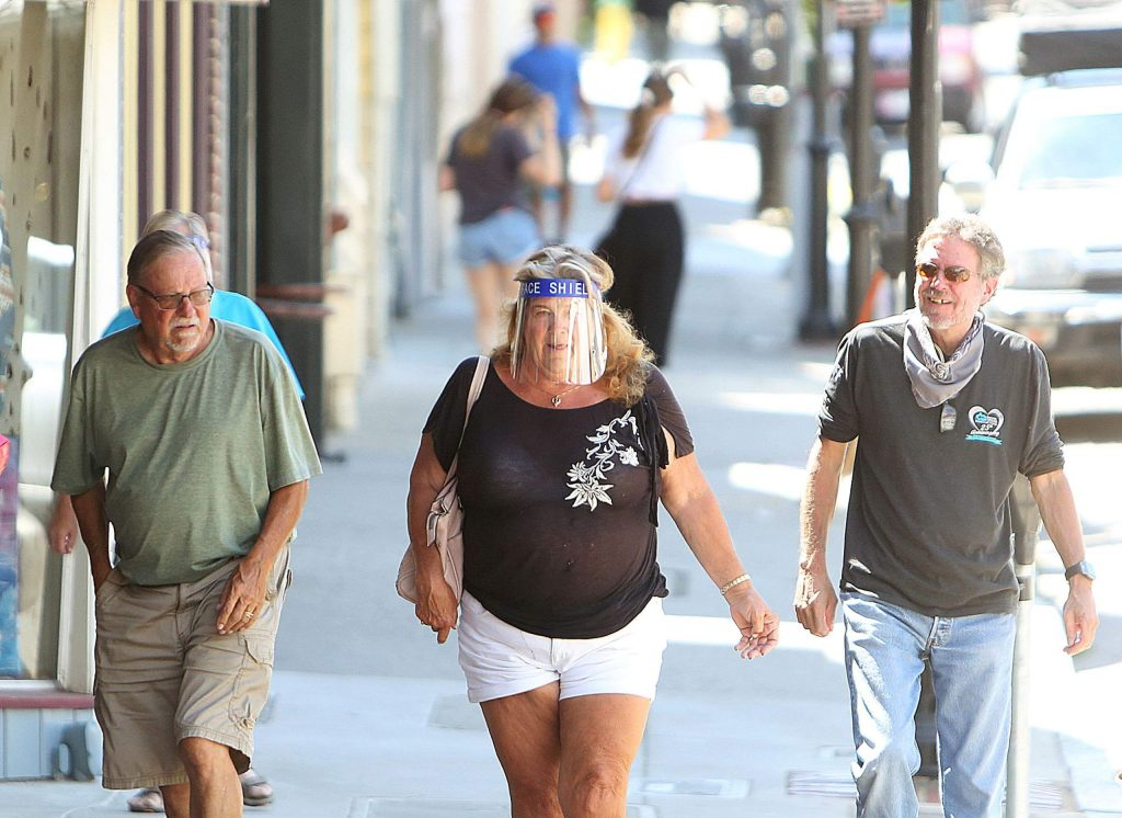 A woman wears a face shield while walking along Broad Street in downtown Nevada City Thursday afternoon.