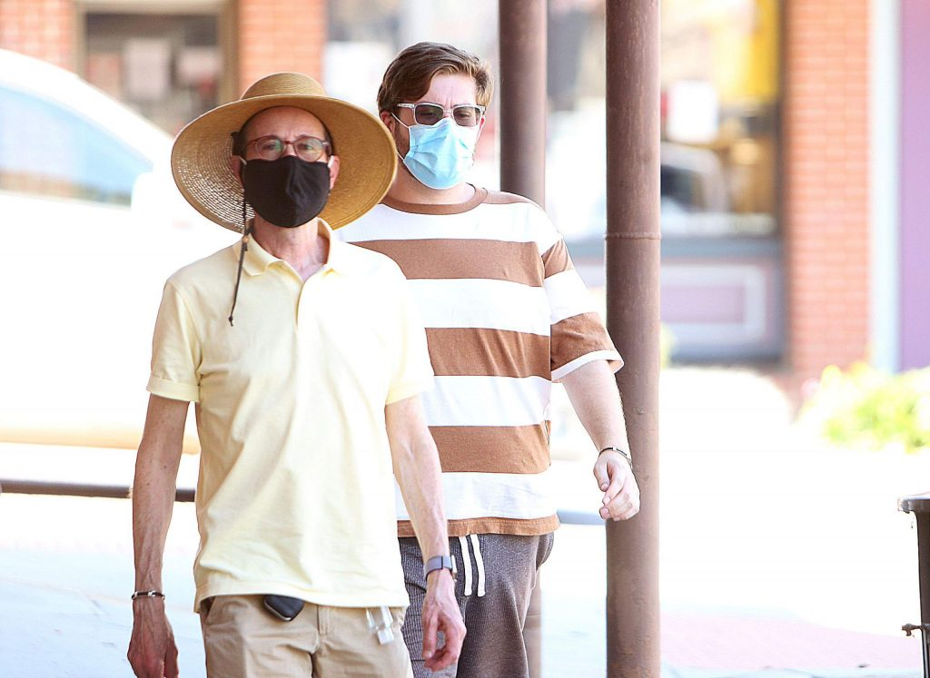 A pair of walkers along Mill Street don their masks while perusing the shops of downtown Grass Valley Thursday.