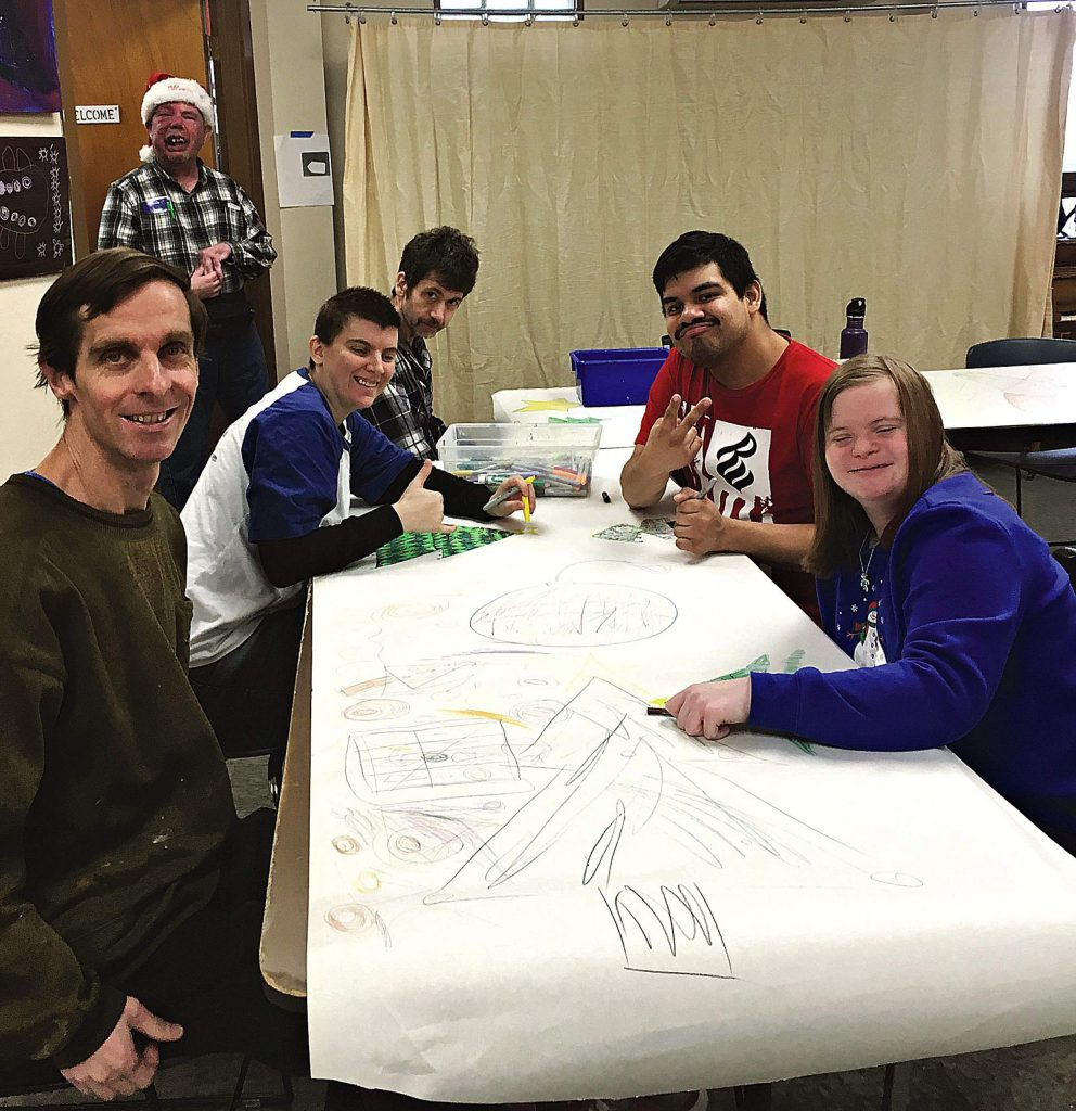 As part of socialization training, NCA artist instructor Wesley James supervises a group art project. From left: James; behind James in Santa hat is Paul Melching; seated at the table are Jenny Crowell, Scott Gregory, Jesus Pozoz and Carlene Stoneman. SUBMITTED PHOTO
