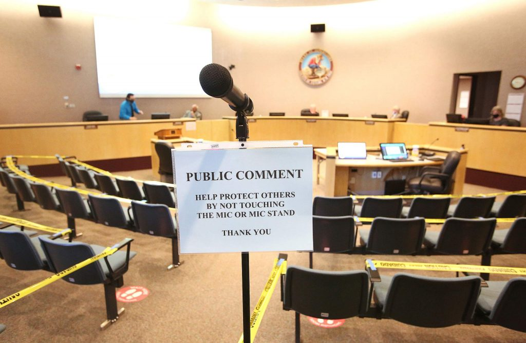 A single microphone placed at the back of the room sits among a nearly empty Nevada County Board of Supervisors meeting Tuesday, the first publicly held meeting since March. Seating was limited to a fraction of the usually available seats to aid in social distancing.