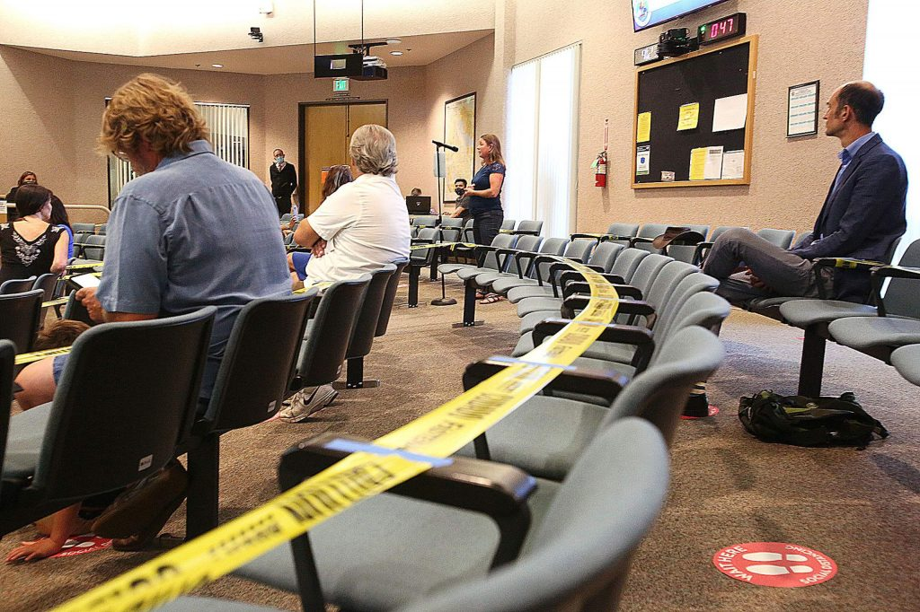 Caution tape separates rows of seating within the supervisor's chambers at the Eric Rood Administrative Center during Tuesday's meeting.