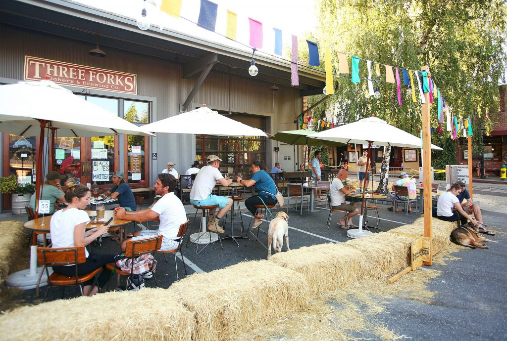 Bales of hay and a string of Tibetan prayer flags surround the outdoor dining area set up outside of Three Forks Bakery and Brewing Co.