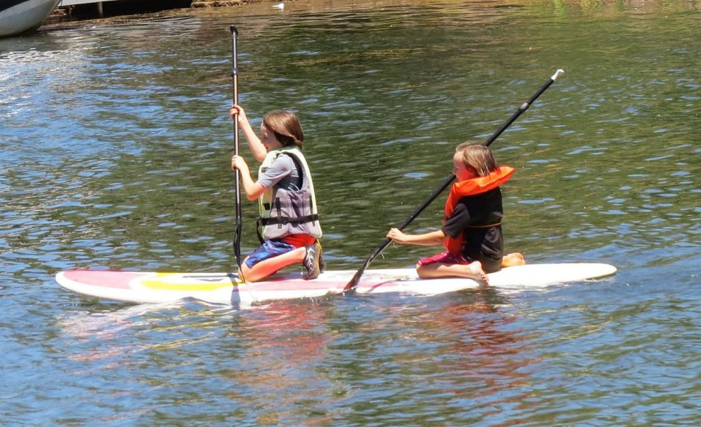 A couple of girls paddling through the water at Lake of the Pines.