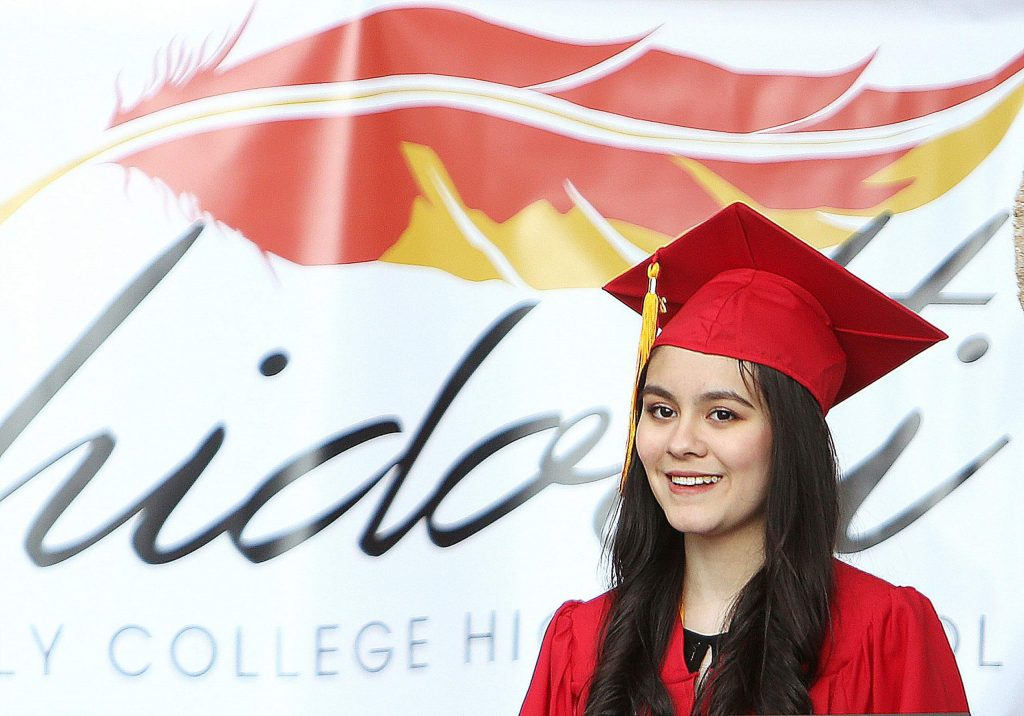 A Ghidotti Early College High School graduate is all smiles as she receives her diploma on the steps at Sierra College.
