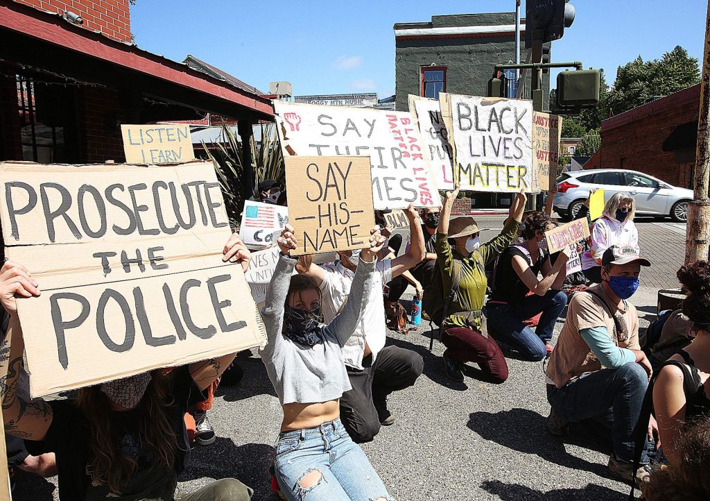 Peaceful protesters kneel in silence on the sidewalks of downtown Grass Valley's South Auburn Street for eight minutes symbolizing the amount of time Minneapolis police officer Derek Chauvin kneeled on the neck of George Floyd..