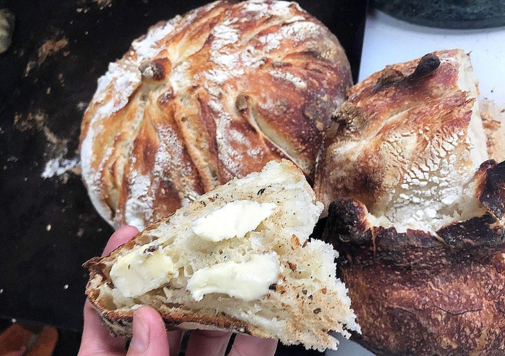 Katrina Schneider, who moderates a local Facebook group for sourdough enthusiasts, shows off one of her loaves of sourdough bread.