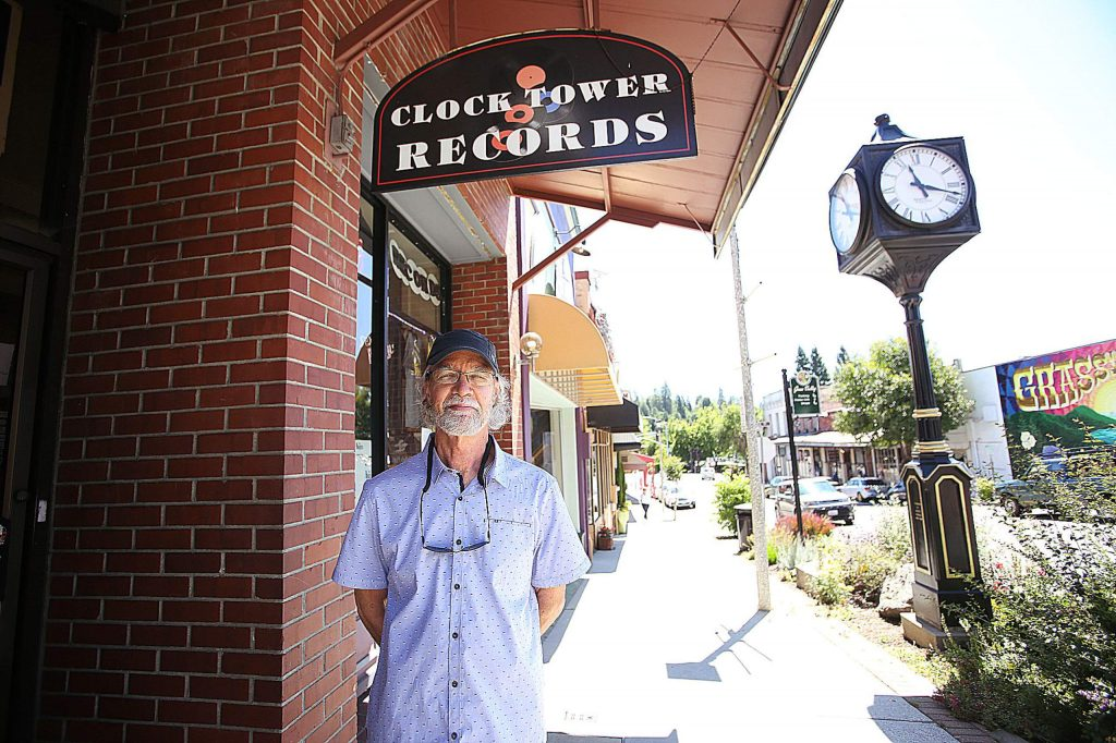 Clock Tower Records' Curt Smith removes his face covering while standing out front of his downtown Grass Valley record store.