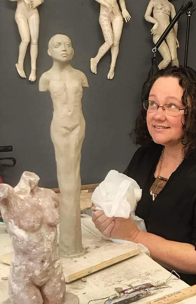 Artist Juliette Williams poses with her sculpture, The Healer.