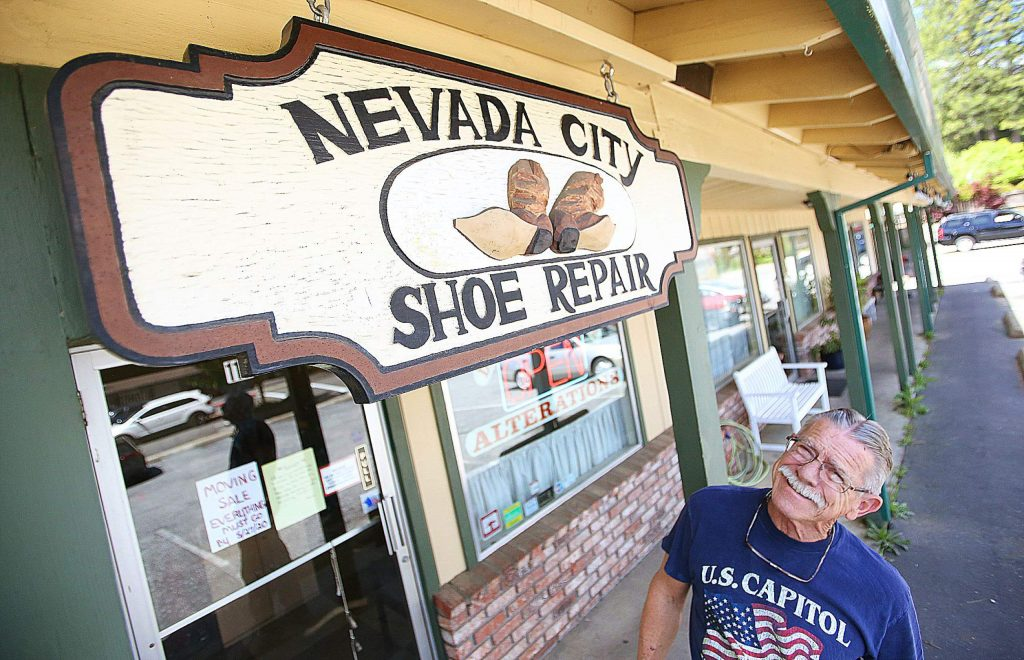 Nevada City Shoe Repair's Frank Pfaffinger looks up at the custom handmade sign that has been hanging over the door of his business for years. Pfaffinger will be closing his brick-and-mortar shop and will be conducting mobile shoe repairs.