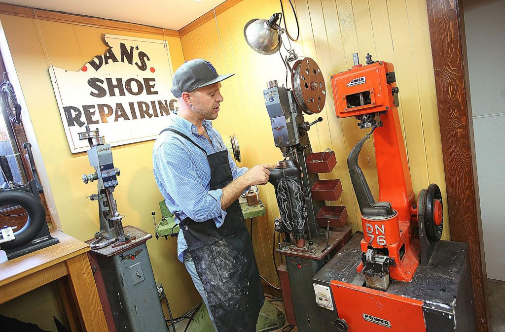 Jacob McDonald of downtown Grass Valley's OxVolk LeatherWerks & Shoe Repair demonstrates the usage of the shoe repair machinery that he's brought into the historic Mill Street shoe repair shop.