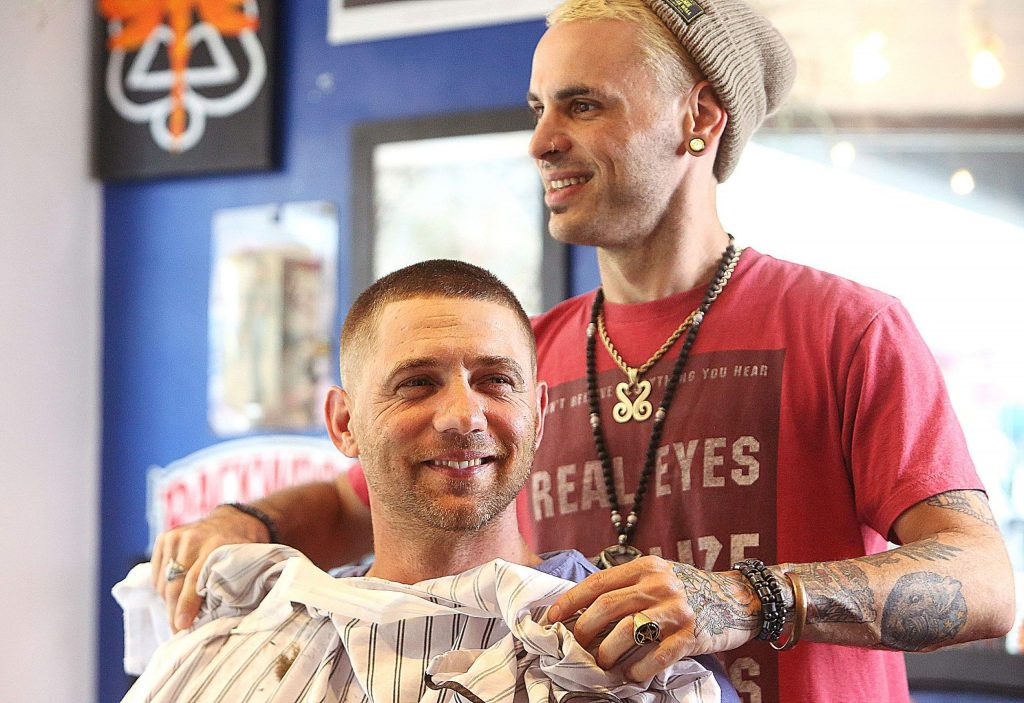 Grass Valley's Rob Kreiter smiles as Amos Seghezzi finishes his first haircut in months in downtown Grass Valley after barbershops and hair salons were allowed to reopen.