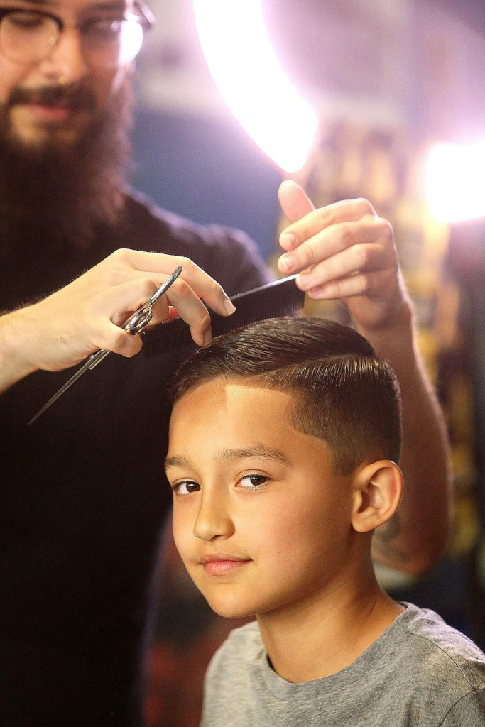 Isaac Montejano puts the finishing touches on Jack Barrientos' haircut Saturday afternoon at Scuzi's in downtown Grass Valley. This is Barrientos' first real haircut in months, aside from a few