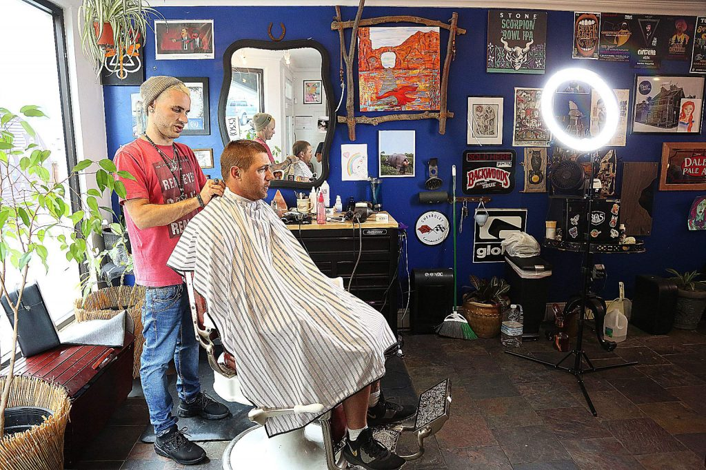 Barber Amos Seghezzi gets to work on Rob Kreiter Saturday afternoon at Scuzi's in downtown Grass Valley. Barbershops and hair salons have been allowed to reopen in Nevada County since Wednesday May 27 when Gov. Gavin Newsom announced an easing of the state's Stage 2 stay-at -home orders.