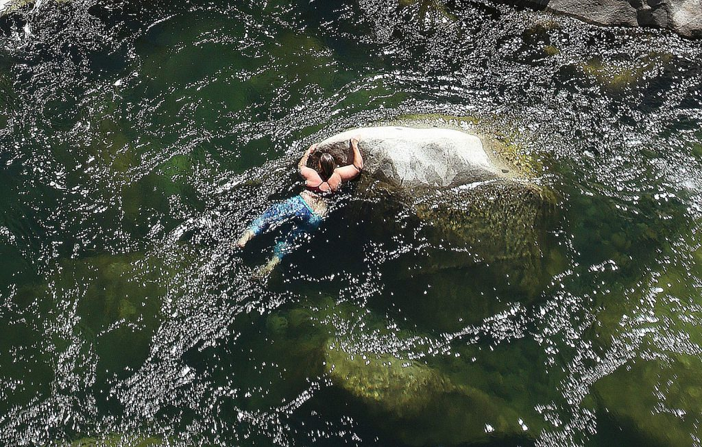 A swimmer holds onto a submerged boulder in the middle of the South Yuba River under the Highway 49 bridge on Tuesday.
