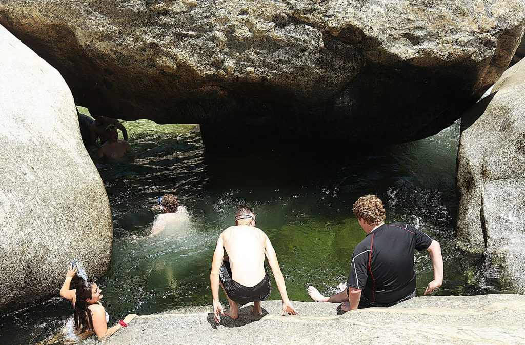 A group of friends from San Luis Obispo takes some time to explore the caves and rock eaves of the South Yuba River near the Highway 49 bridge Wednesday.