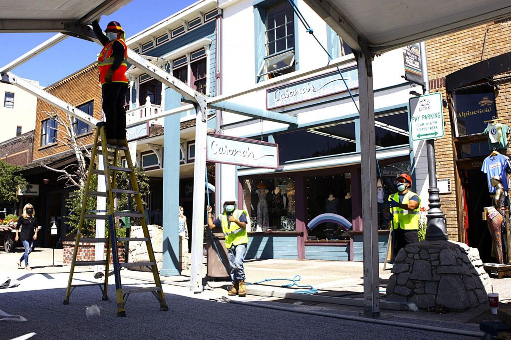 Workers install awnings in downtown Truckee to help provide outdoor space for Pianeta Ristorante so it can remain open to the public, as the governor's order to close restuarants for indoor dining. Prior to the installation, Pianeta was limited to the sidewalk out front and small space near the entrance of the restaurant.