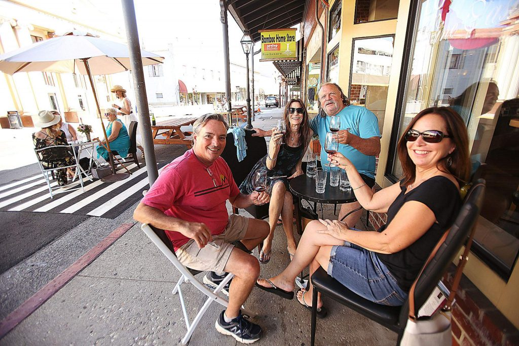 People enjoy a glass of wine out front of Lucchesi Vineyards in downtown Grass Valley Wednesday.