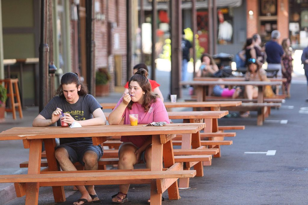 Ethaniel Biggs and Sarah Runge enjoy a tasty treat from a downtown Grass Valley business Wednesday where a section of Mill Street between Main and Bank streets has been blocked off for foot traffic only.